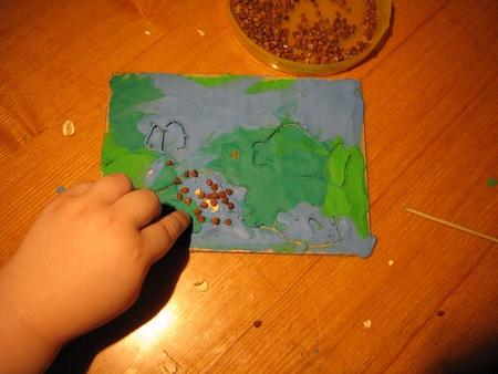 Наполняем первую рыбку на открытке гречневой крупой