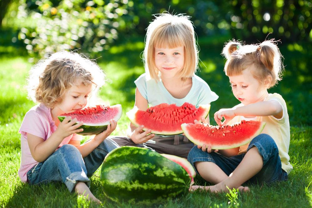 Дети кушают арбуз