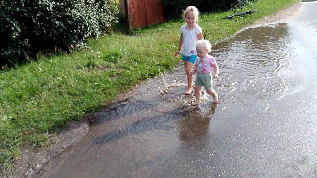 Дети ходят по луже